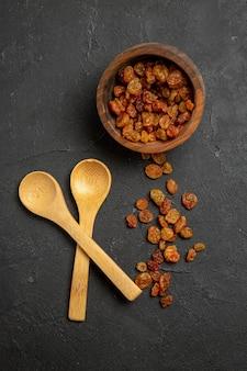 Vue de dessus des raisins secs avec des cuillères en bois sur une surface sombre aux raisins secs