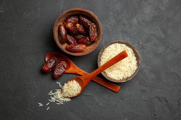 Vue de dessus des raisins secs avec du riz cru sur une surface sombre