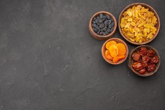 Vue de dessus des raisins secs à l'intérieur de petits pots sur surface grise