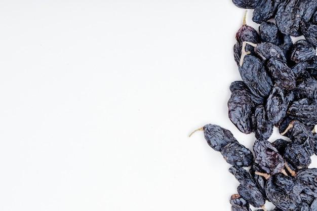 Vue de dessus des raisins secs noirs sur fond blanc avec copie espace