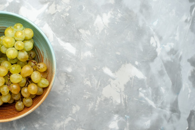 Vue de dessus des raisins verts frais juteux et moelleux à l'intérieur de la plaque sur un bureau léger, jus de fruits frais