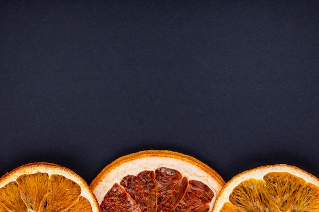 Vue de dessus d'une rangée de tranches d'orange et de pamplemousse séchées disposées sur fond noir