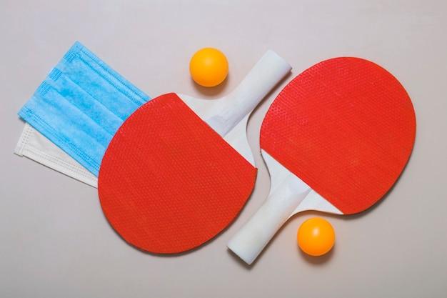 Vue de dessus des raquettes de tennis, des balles et des masques médicaux sur fond beige. divertissement en plein air pendant la quarantaine, pandémie.