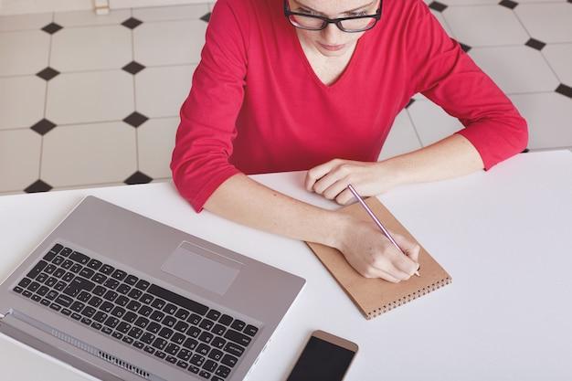 Vue de dessus recadrée d'une écrivaine occupée prend des notes dans le bloc-notes en spirale