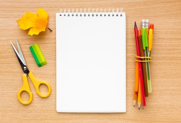 Vue de dessus de la rentrée scolaire avec cahier et ciseaux
