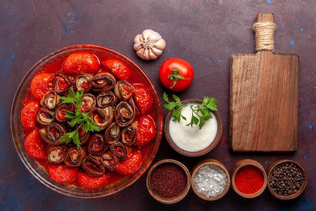 Vue de dessus repas de légumes cuits délicieux tomates et aubergines avec assaisonnements sur la surface sombre