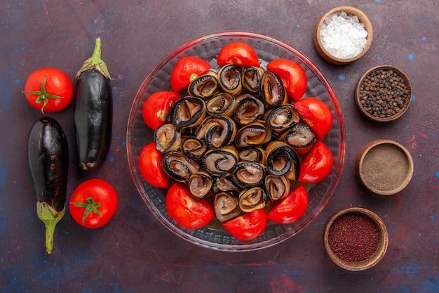 Vue de dessus repas de légumes en tranches et tomates roulées aux aubergines et assaisonnements sur le fond sombre