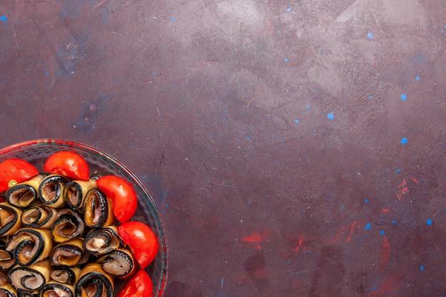Vue de dessus repas de légumes en tranches et tomates roulées aux aubergines sur le fond sombre