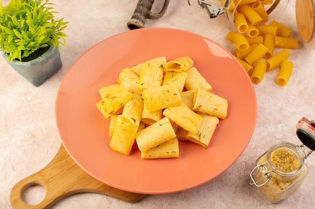 Une vue de dessus un repas savoureux de pâtes italiennes à l'intérieur de la plaque rose avec des fleurs et des pâtes crues sur rose