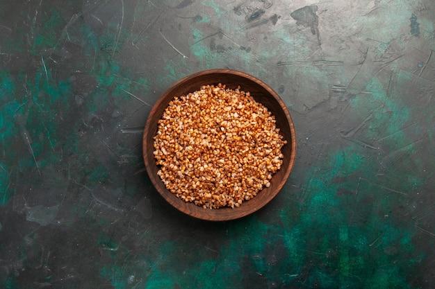 Vue de dessus repas savoureux de sarrasin cuit à l'intérieur de la plaque brune sur la surface vert foncé