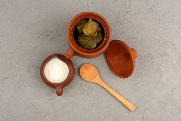Vue de dessus repas de viande verte dolma avec du yaourt sur le plancher gris