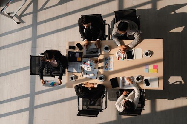 Vue de dessus d'une réunion d'affaires femme leader expliquant les documents avec un groupe de partenaires multiethniques