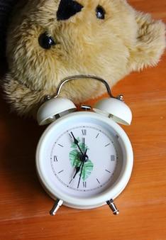 Vue de dessus réveil avec ours brun jouet sur parquet