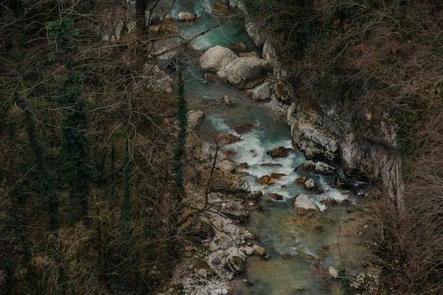Vue de dessus de la rivière forestière qui coule parmi les rochers dans le canyon de martvili