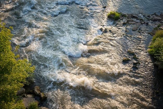 Vue de dessus de la rivière de montagne turbulente et rapide par une journée d'été ensoleillée
