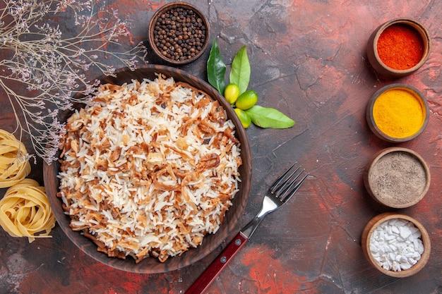 Vue de dessus riz cuit avec assaisonnements sur plat de nourriture de surface sombre repas photo sombre