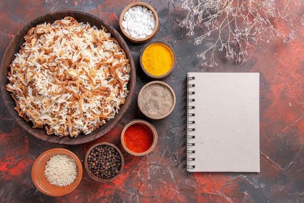 Vue de dessus riz cuit avec assaisonnements sur sol sombre repas plat photo nourriture sombre