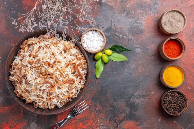Vue de dessus riz cuit avec des assaisonnements sur une surface sombre photo plat alimentaire sombre