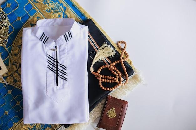 Vue de dessus de la robe traditionnelle musulmane et des perles de prière sur le tapis de prière avec le livre saint al coran il y a une lettre arabe qui signifie le livre saint