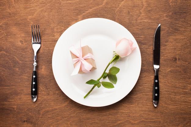 Vue de dessus rose et cadeau sur une assiette