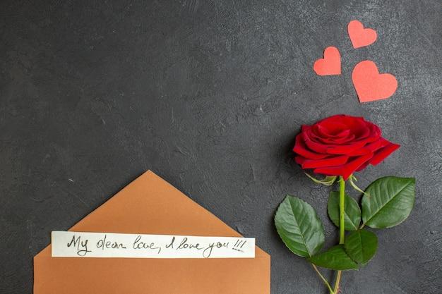 Vue de dessus rose rouge avec une belle note sur fond sombre amour couple passion saint valentin couleur coeur mariage