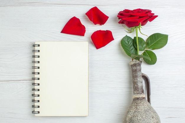 Vue de dessus rose rouge avec bloc-notes sur fond clair sentiment de mariage passion couple amour amant couleur du coeur
