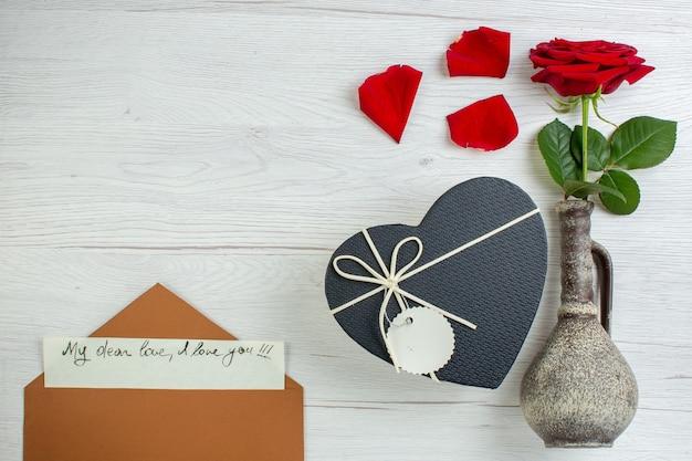 Vue de dessus rose rouge avec présent en forme de coeur sur fond blanc sentiment de mariage passion couple amour amant couleur du coeur