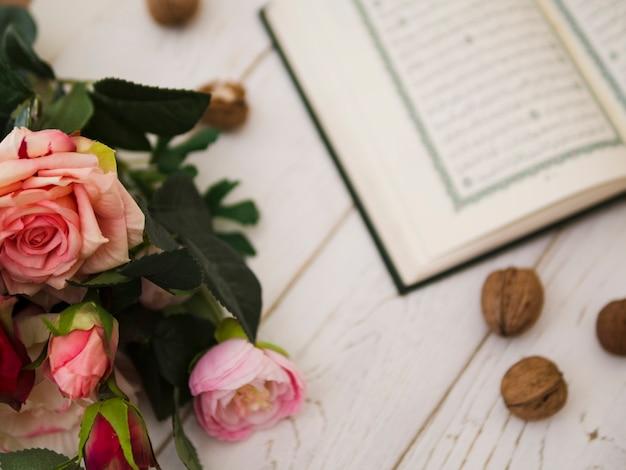 Vue de dessus des roses roses à côté du coran