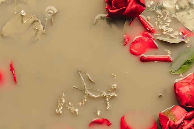 Vue de dessus des roses rouges et des pétales dans de l'eau colorée brune