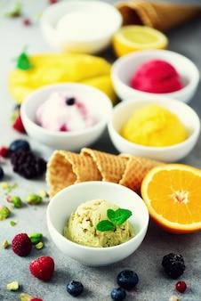Vue de dessus rouge, rose, jaune, vert, boules de crème glacée dans des bols, cônes de gaufres, baies, orange, mangue, pistache