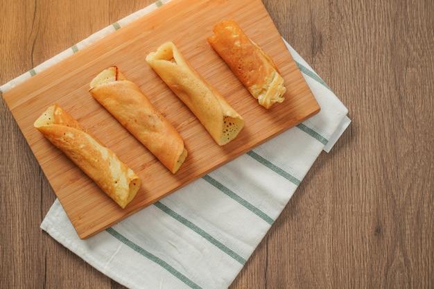 Vue de dessus, rouleau de crêpes rempli de saveurs assorties sur une planche à découper en bambou placé sur un tissu rayé blanc et vert sur une table en bois