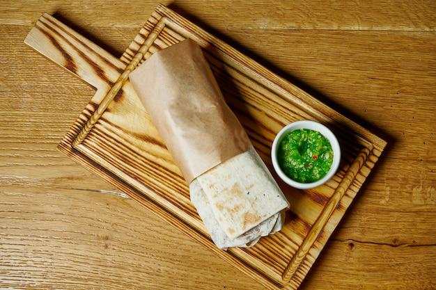 Vue de dessus rouleau frais dans du pain pita avec brochette de poulet, sauce et légumes sur une planche de bois. l'alimentation de rue. shaurma ou shawerma