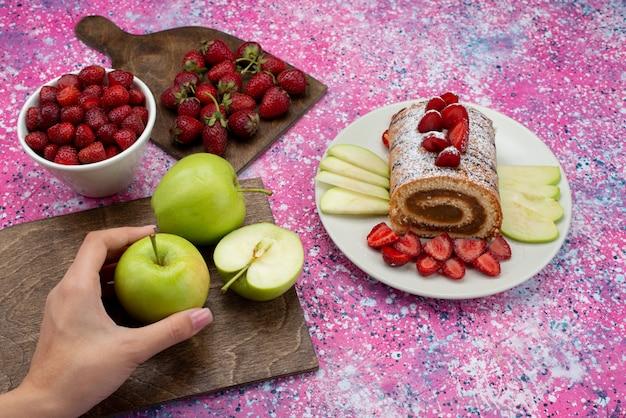 Vue de dessus rouleau gâteau à l'intérieur de la plaque avec des pommes et des fraises sur le bureau de couleur biscuit gâteau aux fruits sucrés