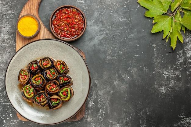 Vue de dessus des rouleaux d'aubergine farcis dans une assiette ovale blanche au curcuma dans un bol sur un plateau de service en bois adjika sur fond gris