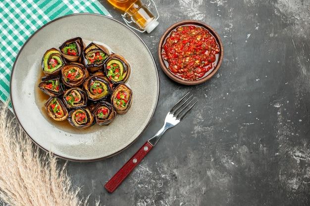 Vue de dessus des rouleaux d'aubergine farcis dans une assiette ovale blanche une fourchette bouteille d'huile adjika sur fond gris