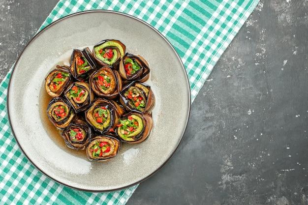 Vue de dessus des rouleaux d'aubergine farcis dans une assiette ovale blanche nappe blanc turquoise sur fond gris avec espace de copie