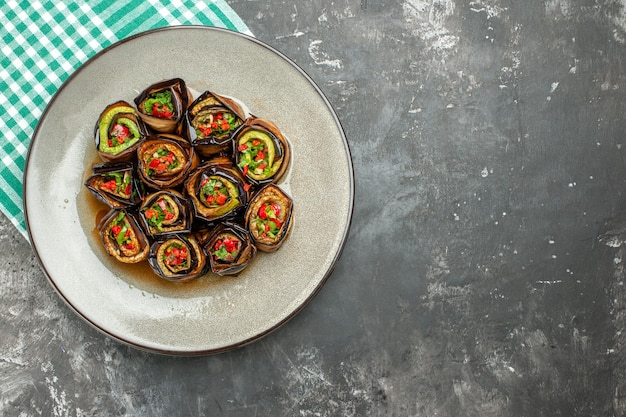 Vue de dessus des rouleaux d'aubergine farcis dans une assiette ovale blanche nappe blanc turquoise sur fond gris avec place libre