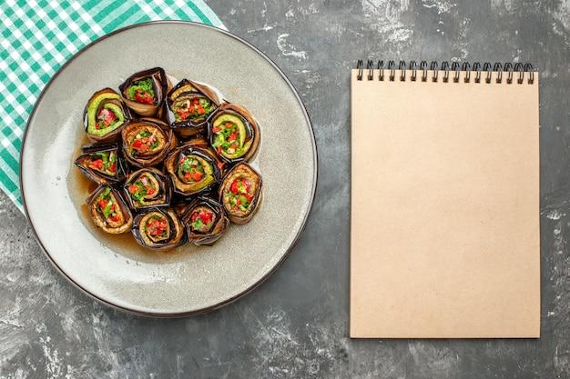 Vue de dessus des rouleaux d'aubergine farcis dans une assiette ovale blanche nappe turquoise-blanc un cahier sur fond gris