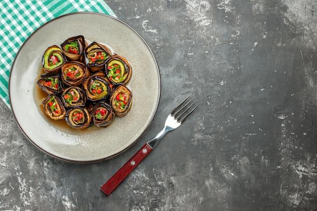 Vue de dessus des rouleaux d'aubergine farcis dans une assiette ovale blanche nappe turquoise-blanc une fourchette sur une surface grise