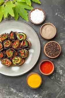 Vue de dessus des rouleaux d'aubergines farcies sur une assiette blanche différentes épices dans de petits bols sur fond gris