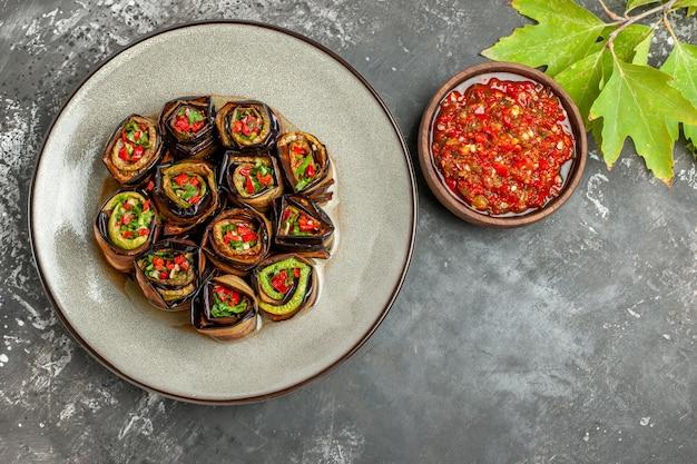 Vue de dessus des rouleaux d'aubergines farcies sur une assiette blanche, une fourchette et un couteau adjika sur une surface grise