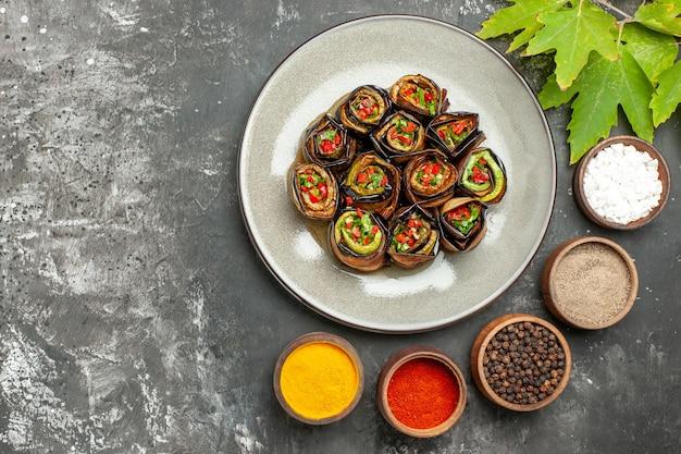 Vue de dessus des rouleaux d'aubergines farcies sur une assiette ovale blanche différentes épices dans de petits bols feuilles de platane sur une surface grise