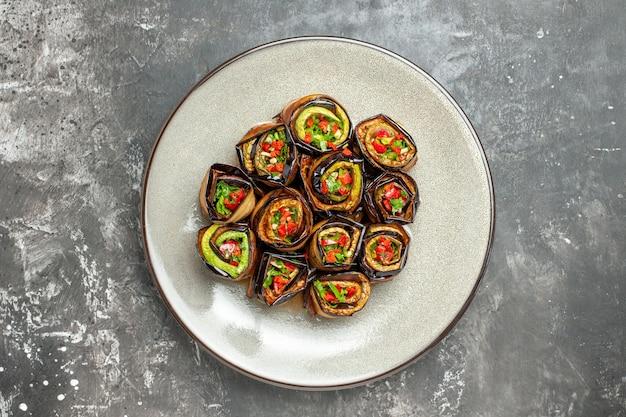 Vue de dessus des rouleaux d'aubergines farcies sur une assiette sur une surface grise