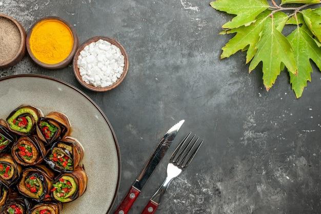Vue de dessus des rouleaux d'aubergines farcies au curcuma en poudre de piment dans de petits bols laisse une fourchette et un couteau sur une surface grise
