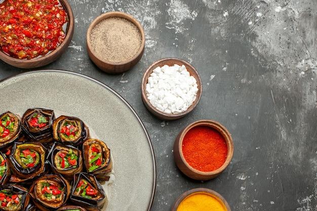 Vue de dessus des rouleaux d'aubergines farcies dans une assiette ovale blanche épices dans de petits bols sel poivre poivre rouge curcuma adjika sur surface grise