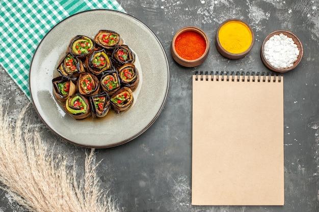 Vue de dessus rouleaux d'aubergines farcies dans une assiette ovale blanche nappe blanc turquoise différentes épices un cahier sur une surface grise