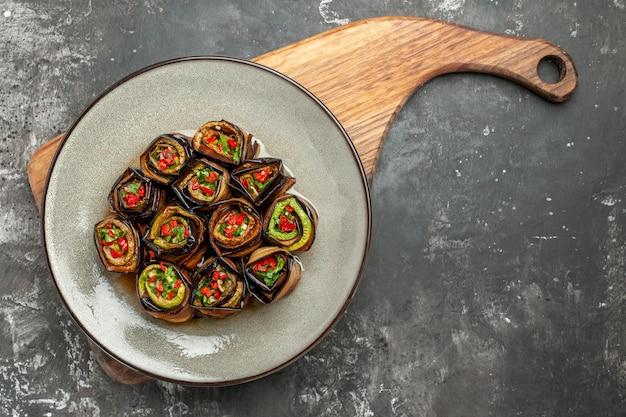 Vue de dessus des rouleaux d'aubergines farcies dans une assiette ovale blanche sur une planche de service en bois avec poignée sur une surface grise