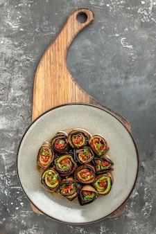 Vue de dessus des rouleaux d'aubergines farcies dans une assiette ovale blanche sur un plateau de service en bois avec poignée sur fond gris