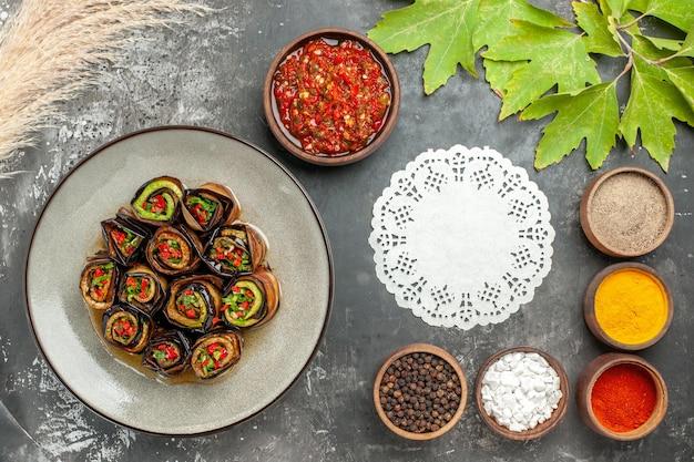 Vue de dessus des rouleaux d'aubergines farcies différentes épices adjika dans de petits bols napperon ovale en dentelle blanche sur une surface grise