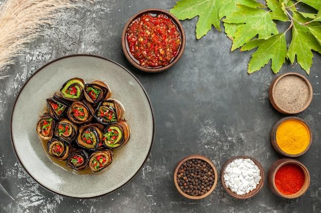 Vue de dessus des rouleaux d'aubergines farcies différentes épices adjika dans de petits bols sur une surface grise